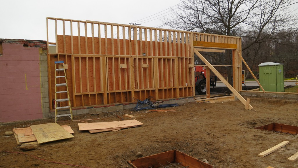 New exterior wall framing has begun to support the new raised roof structure.